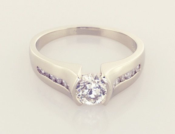 Solitaire surrounded by channel set round brilliant diamonds in 18KT white gold
