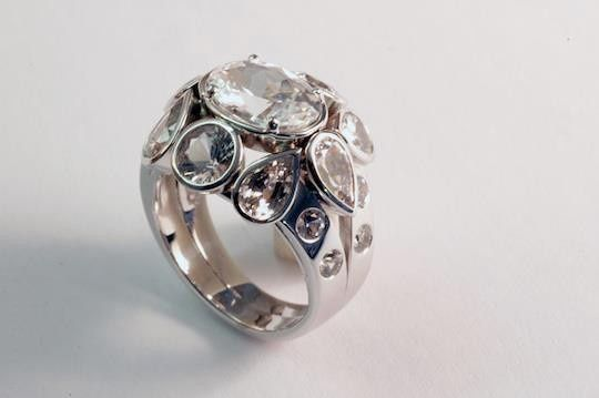Our cluster design ring in white gold, made to fit the clients budget by utilizing sapphires over...