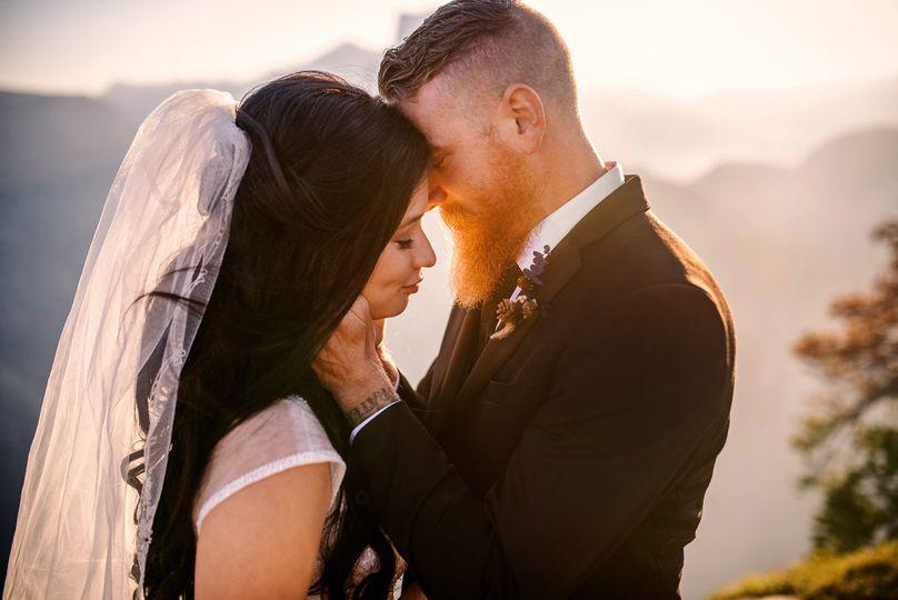 Wedding couple enjoying the sunset photos in the mountains.