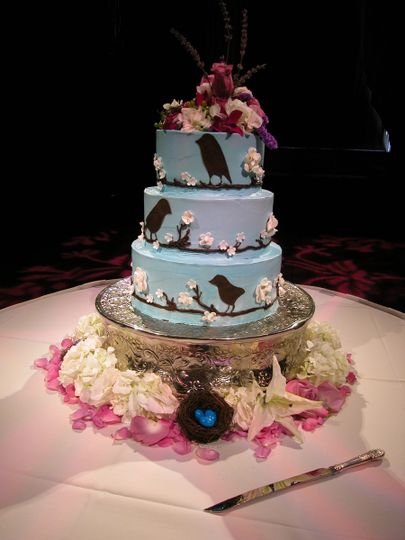 Chocolate Birds and Sugar Flowers adorn this Italian Buttercream wedding cake, then finished with...