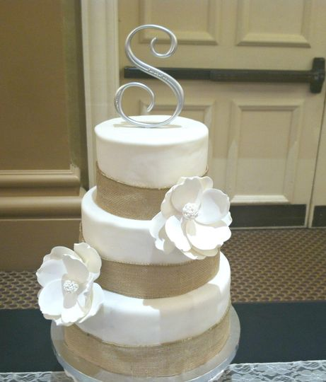 A 3 tier Nashville Wedding Cake covered in fondant,surrounded in  burlap ribbon. Decorated fondant...