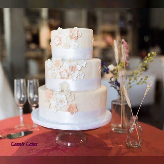 A 3 tier Nashville Wedding Cake covered in peach  fondant blossom flowers surrounded in white...