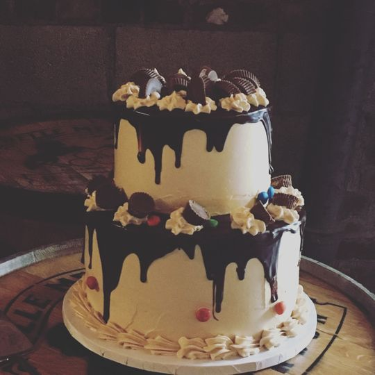 2 tier chocolate peanut butter grooms cake frosted with peanut butter butter cream and dripping with...