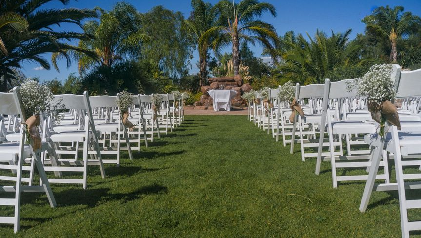 Outdoor ceremony area with view from aisle looking toward water feature.
