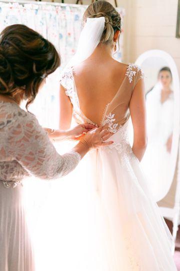 Mom buttoning wedding dress