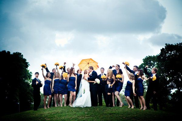 Newlyweds with wedding attendants and umbrellas