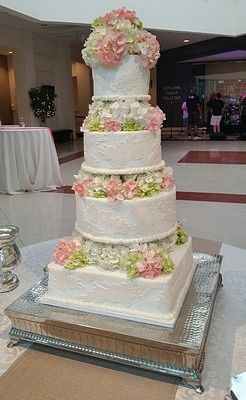 Tall multi-shaped cake with lace and hydrangeas in the atrium of the Columbia Museum of Art.