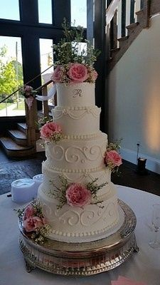 Fresh heirloom roses on a five-tier buttercream cake create an elegant focal point at 701 Whaley.