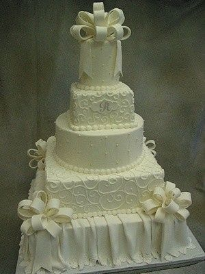 White multi-shaped tower.  All buttercream except for bows, monogram plaque and bottom tier skirt.
