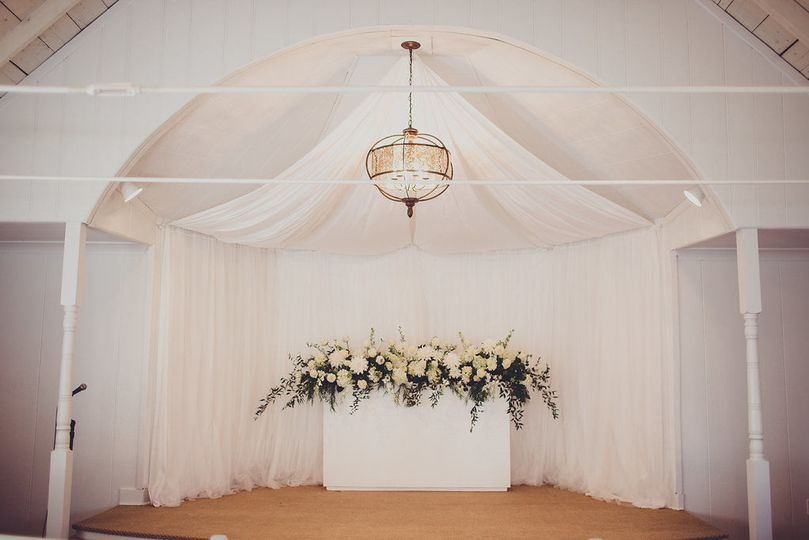 Drapery installation and floral artistry design for a wedding ceremony at the most darling little...