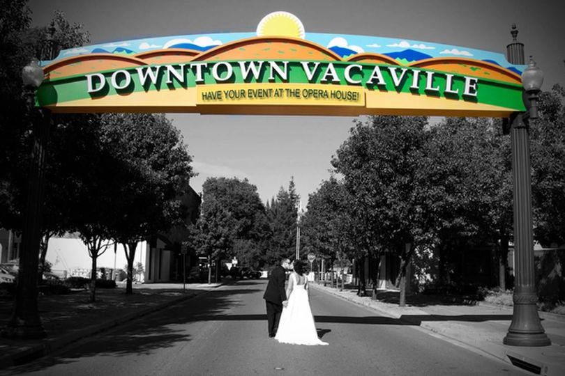 Photography by Kelly Murray Bride and groom under Vacaville sign on Davis st. Opera House in...
