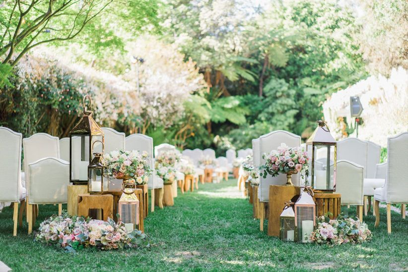 romantic outdoor wedding ceremony with blush roses and lanterns