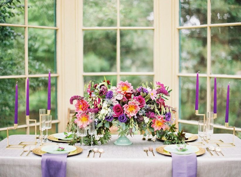 purple gold and pink wedding centerpiece with candles and greenery