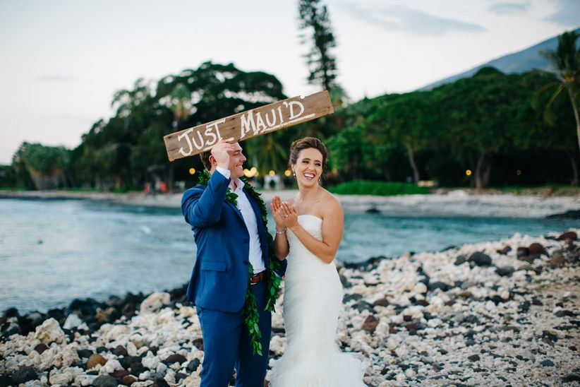 bride and groom standing on beach holding wooden sign that says