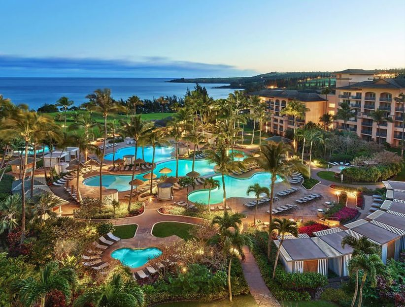 aerial view of resort with swimming pools and guest bungalows overlooking the ocean