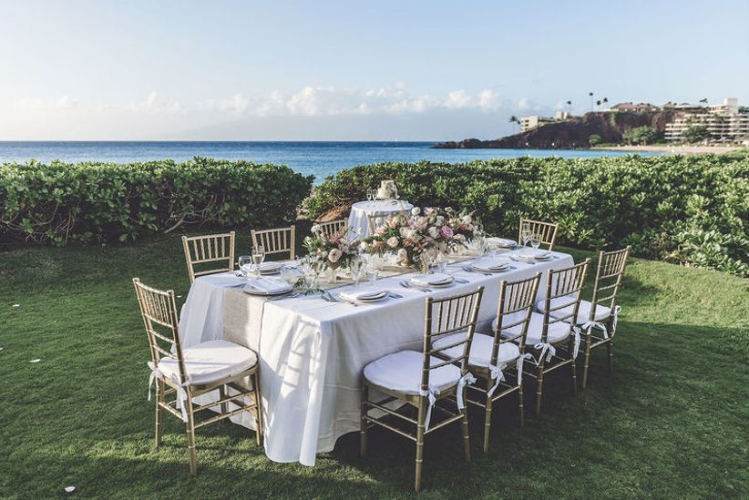 intimate reception dinner table outside near the ocean