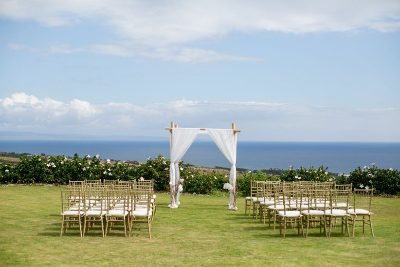 outdoor wedding ceremony overlooking the ocean with fabric and flower arch at the altar