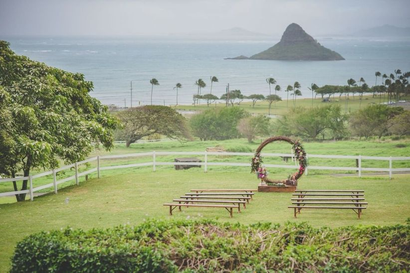 outdoor oahu wedding ceremony overlooking the ocean with mountains in the distance