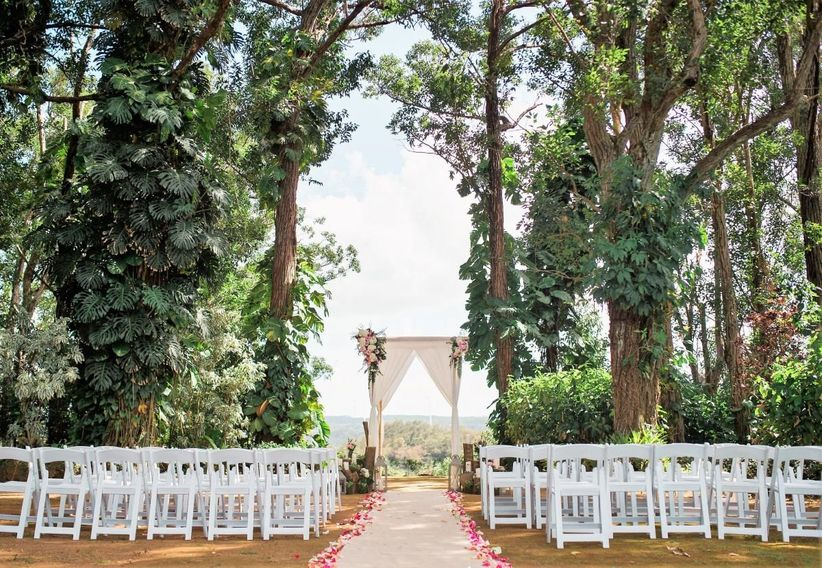scenic outdoor wedding ceremony beneath shady trees on top of a hill overlooking the valley and ocean in the distance