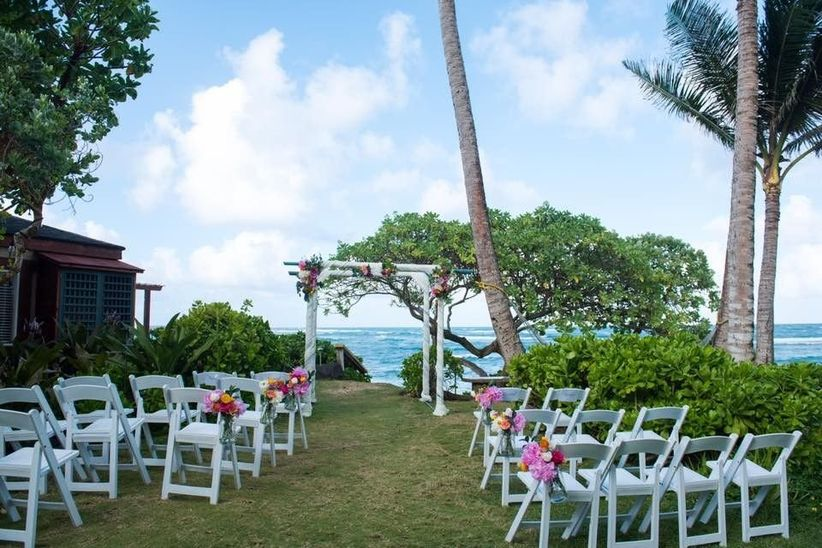 oceanfront wedding ceremony with white folding chairs and gazebo decorated with pink tropical flowers