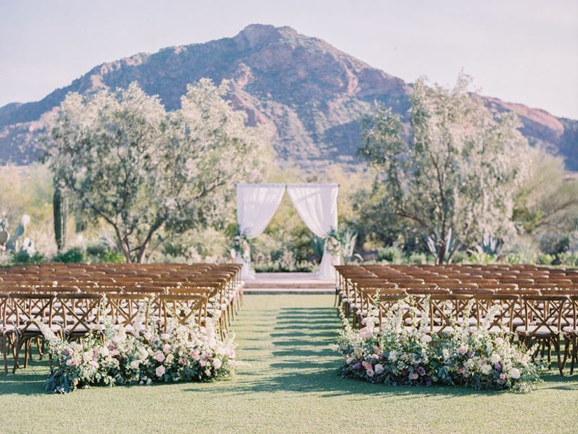 outdoor wedding ceremony with flower aisle markers and fabric arch