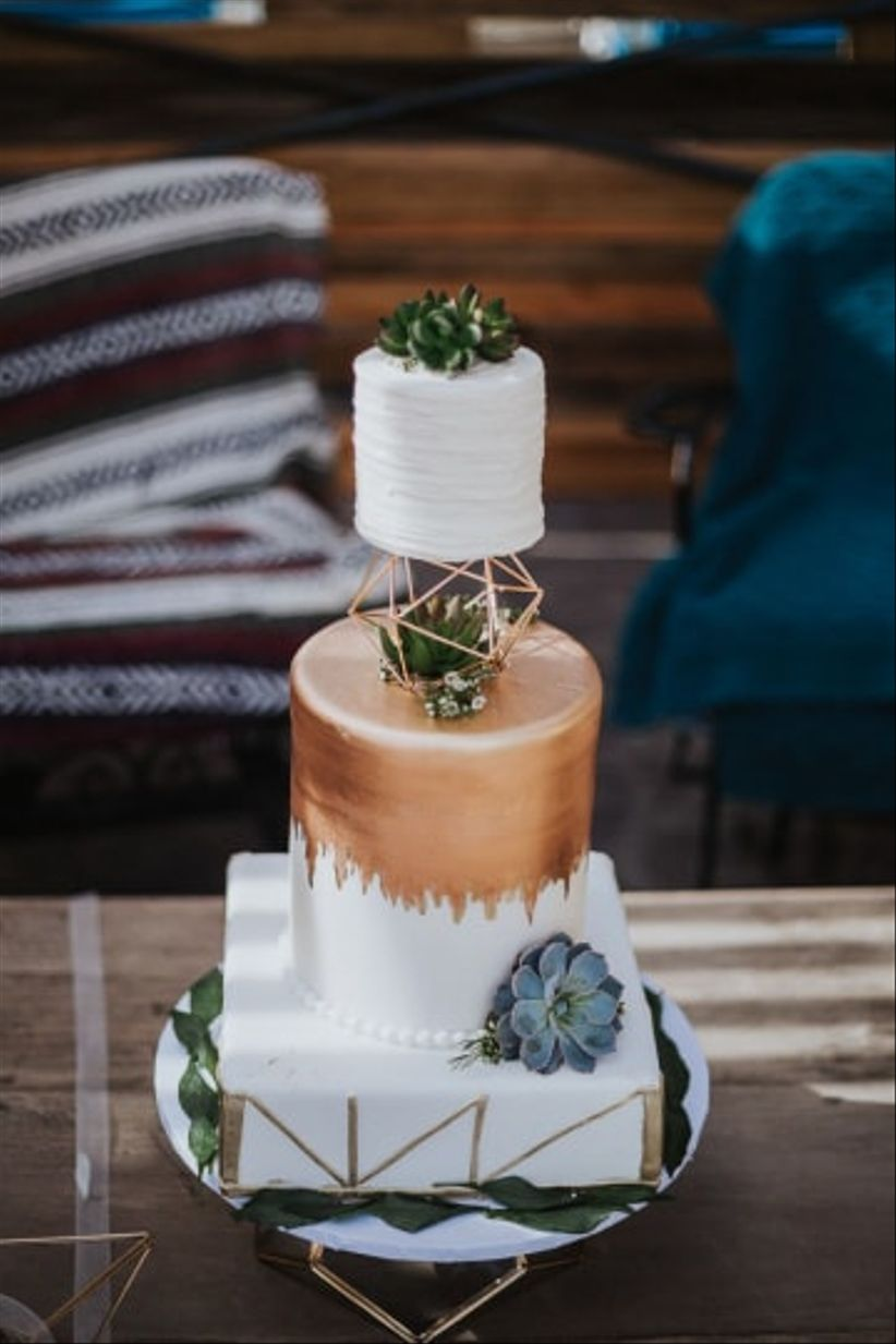 white fondant cake with copper and geometric decorations