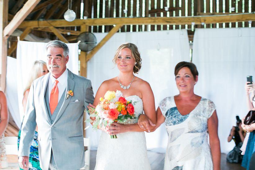 bride walking down aisle with parents