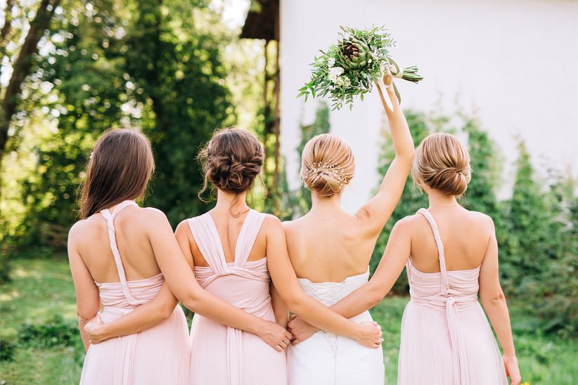 bridesmaids in pink dresses backs turned