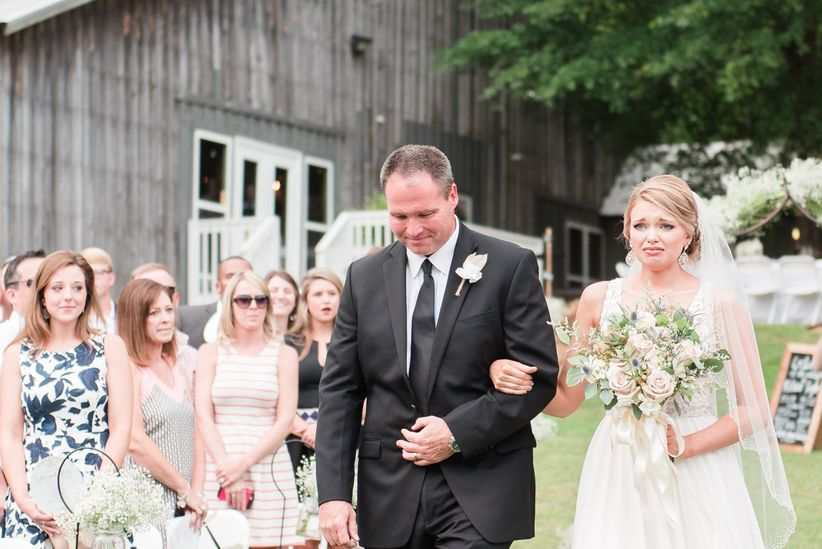 bride walking down aisle and crying