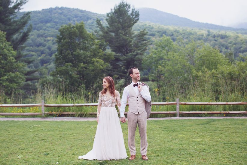 wedding couple holding hands with mountain backdrop