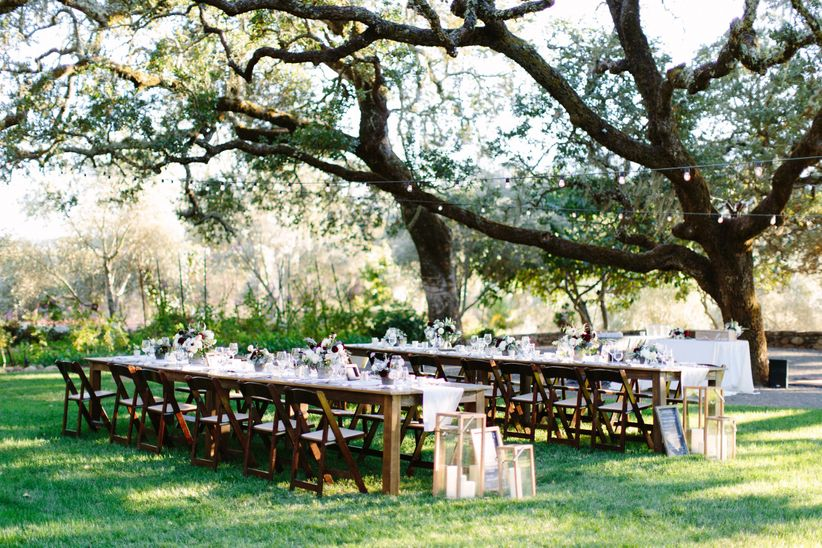 romantic outdoor reception space beneath large shady tree at garden wedding venue