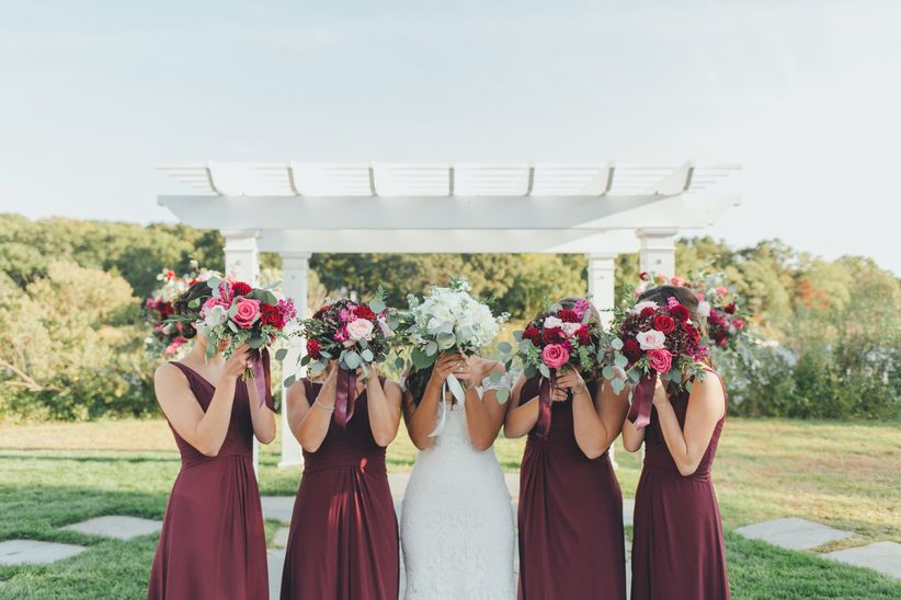 bridesmaids with bouquets covering faces