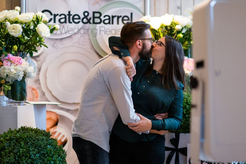 The wedding registry checklist every couple needs weddingwire couple kissing in front of crate and barrel sign junglespirit Choice Image
