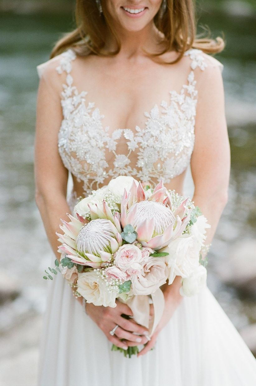 bride holding bouquet with pink proteas and roses
