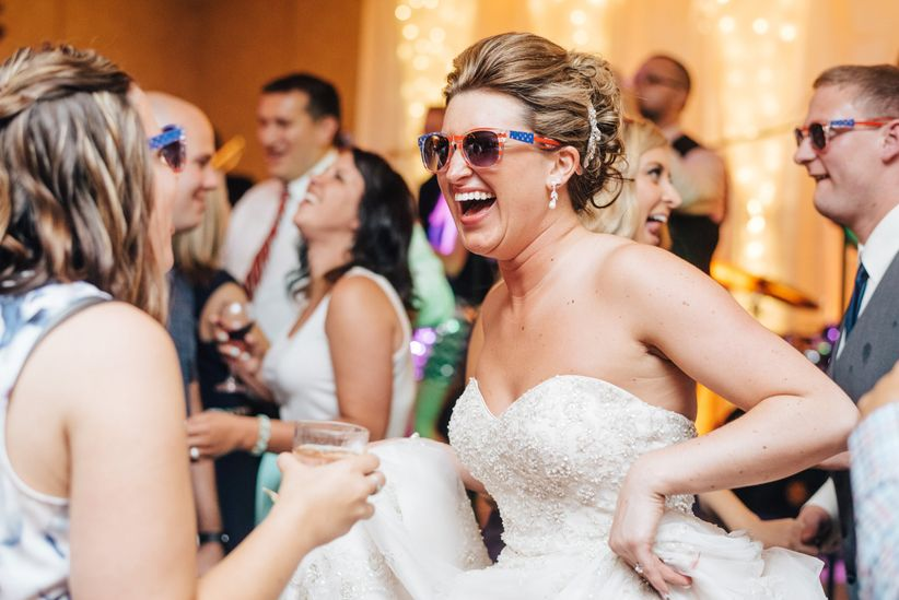 bride wearing sunglasses and dancing at wedding