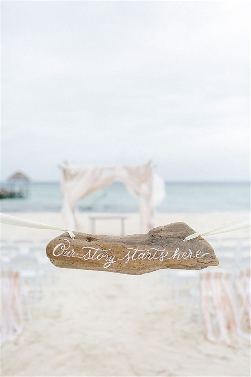 beach wedding ceremony with driftwood sign that reads