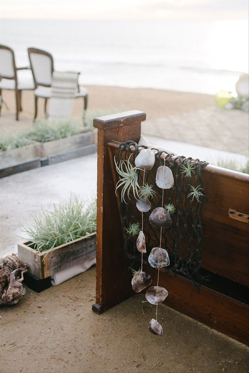 wedding pews at the beach decorated with seashells and fishing net