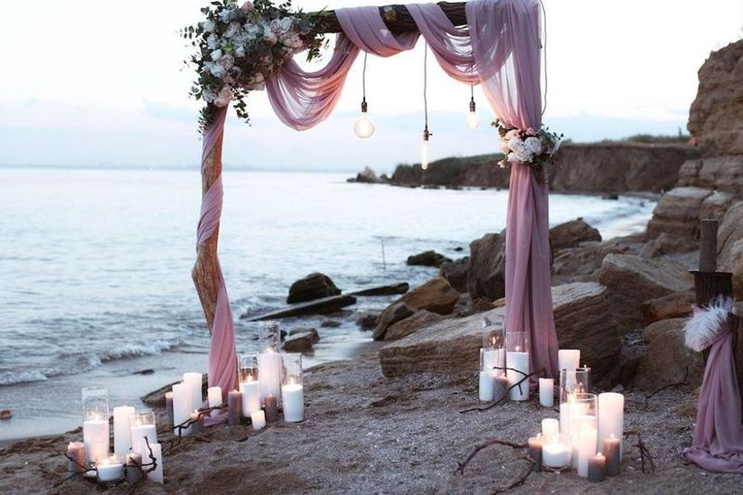 beach wedding ceremony site next to the water decorated with flowy purple fabric and candles