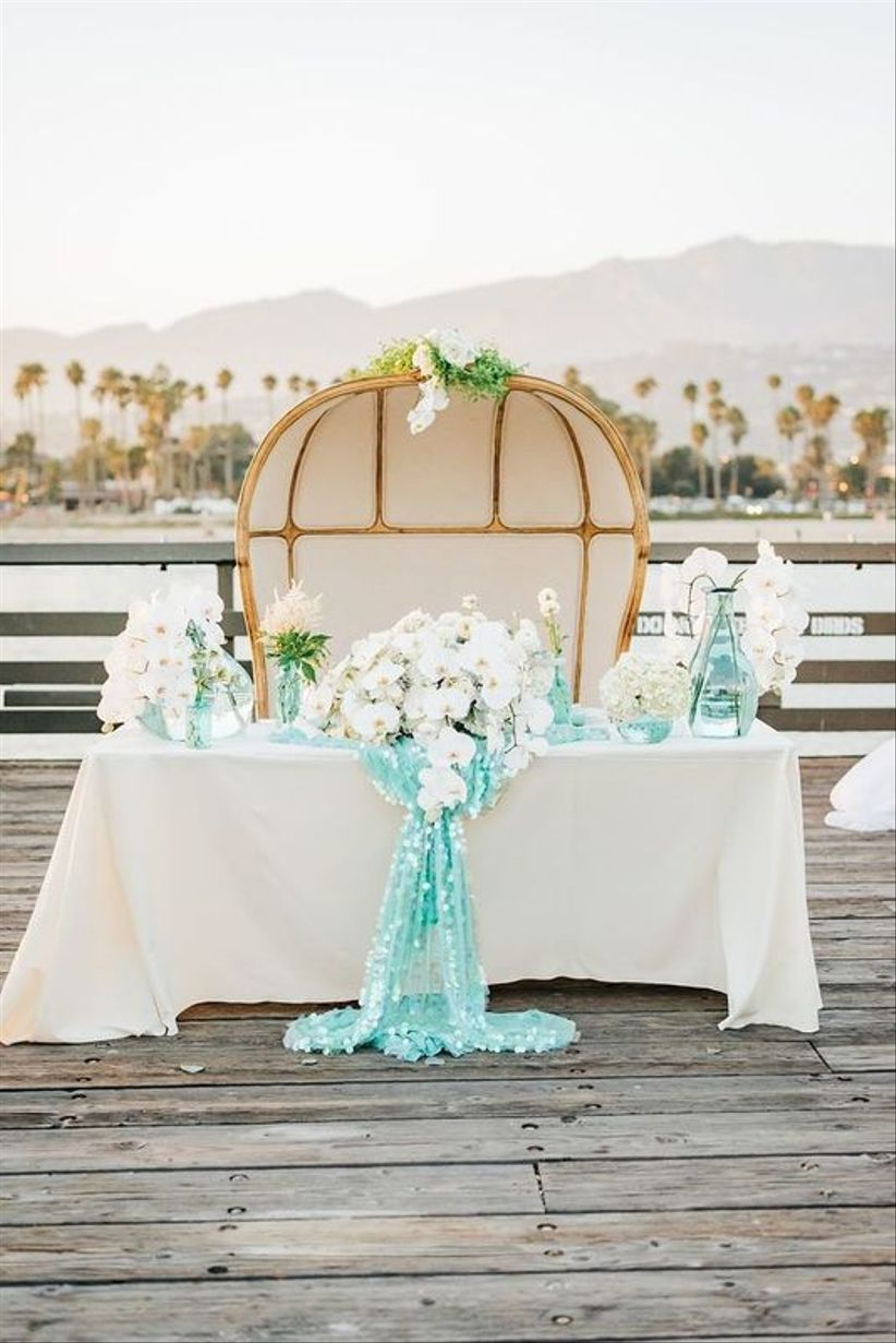 sweetheart table decorated with white and turquoise sequin tablecloth