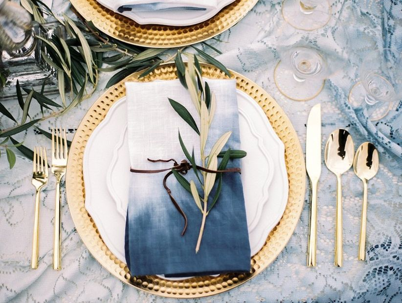 gold and white wedding place setting with blue ombre napkin and greenery