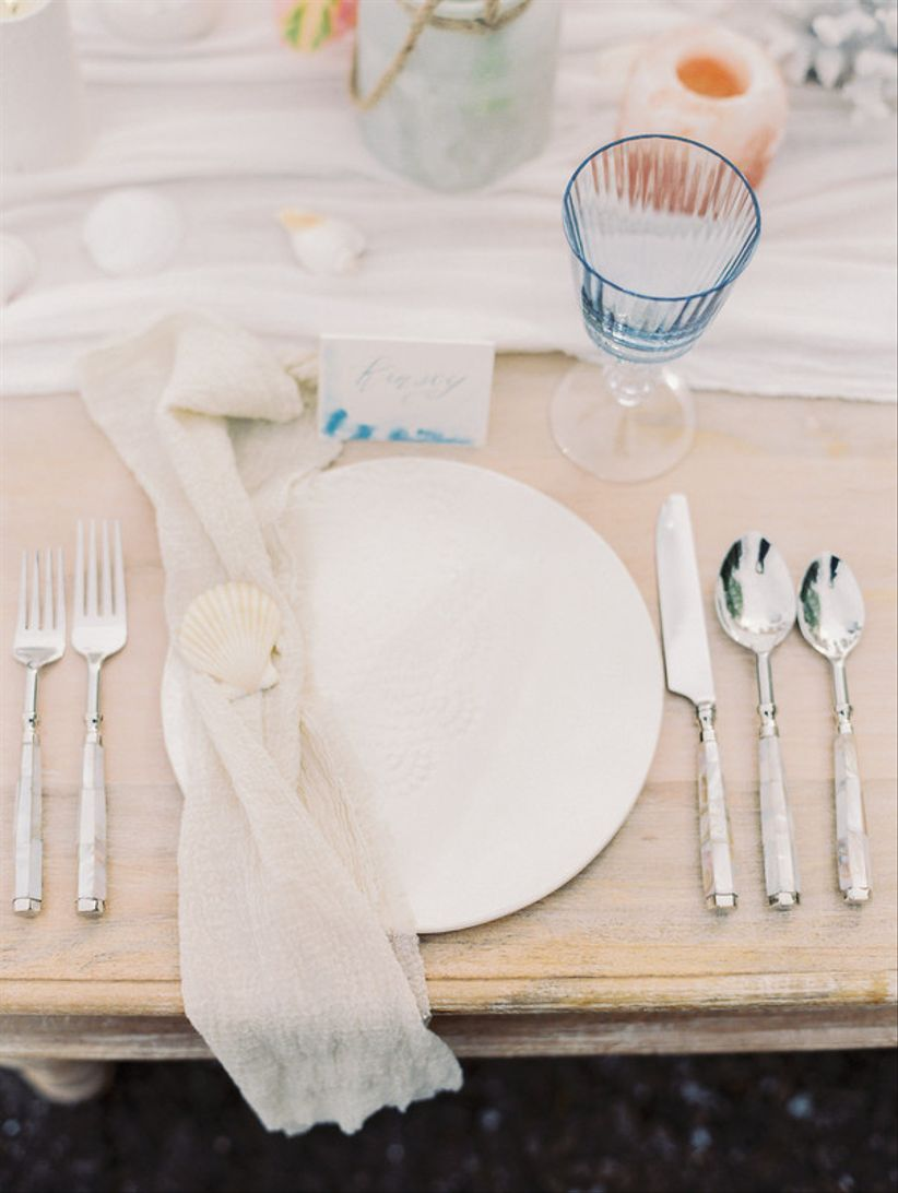 wedding reception place setting with neutral colors and seashells