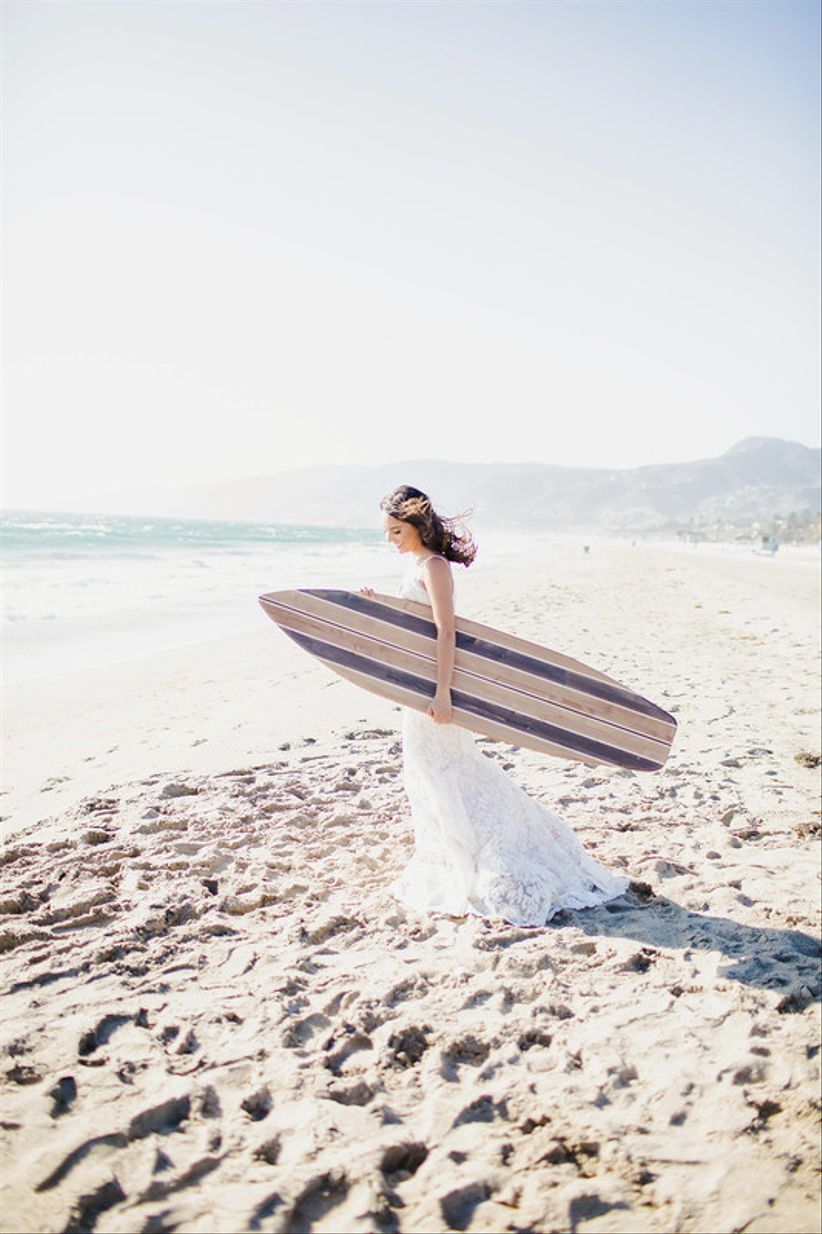 bride on the beach carrying a surfboard