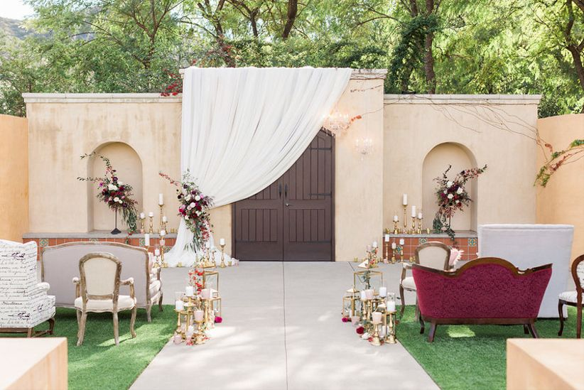 romantic outdoor ceremony space at santa barbara wedding venue with antique red couches and red roses