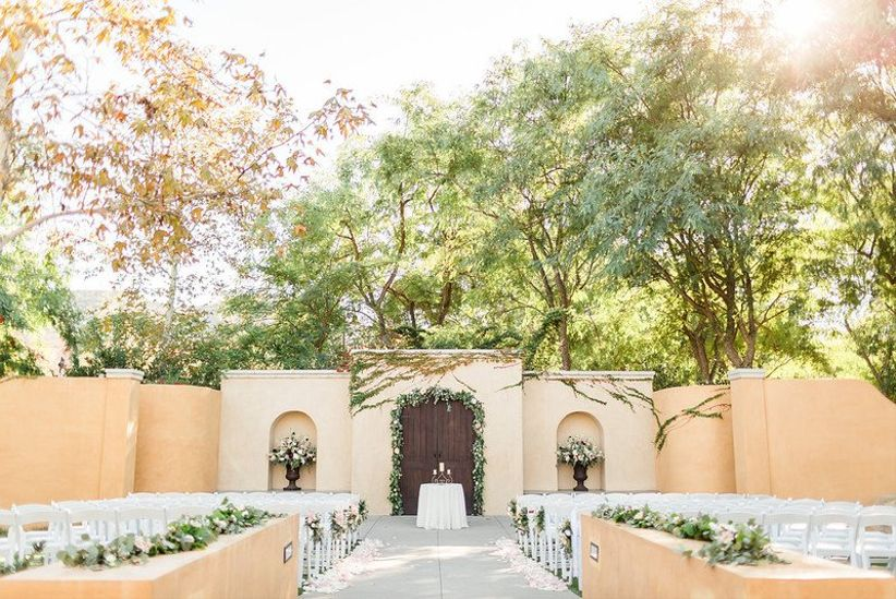 Los Robles Greens santa barbara wedding venue outdoor patio with rows of white chairs decorated with greenery floral garlands