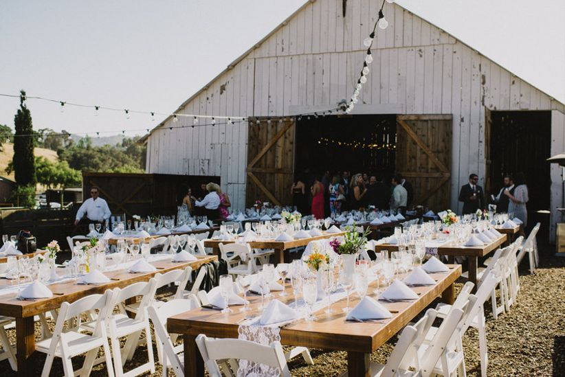 rustic santa barbara wedding venue large white barn in the background with long banquet tables and chairs set up for reception