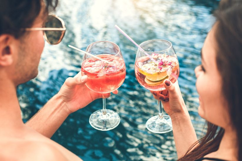 couple toasting cocktails in pool