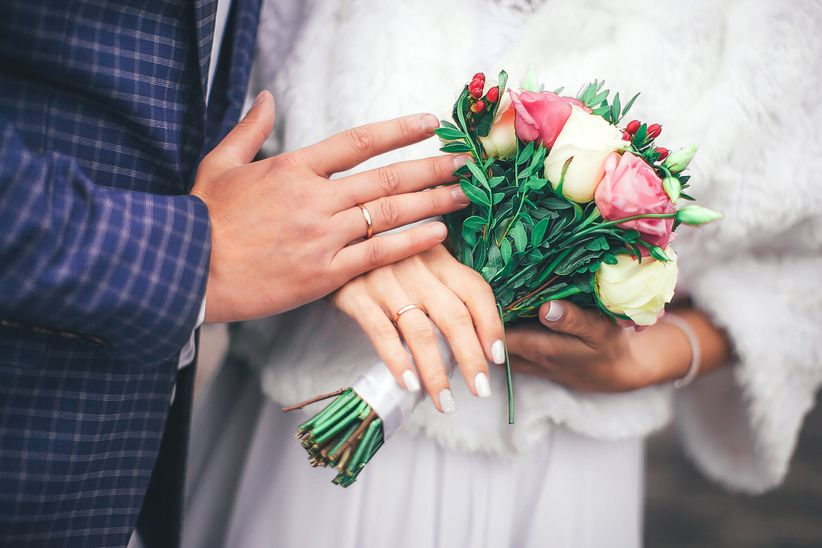couple holding bouquet wedding rings