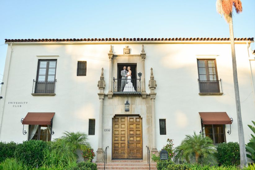 bride and groom kiss outside on the balcony at historic mansion wedding venue in Santa Barbara