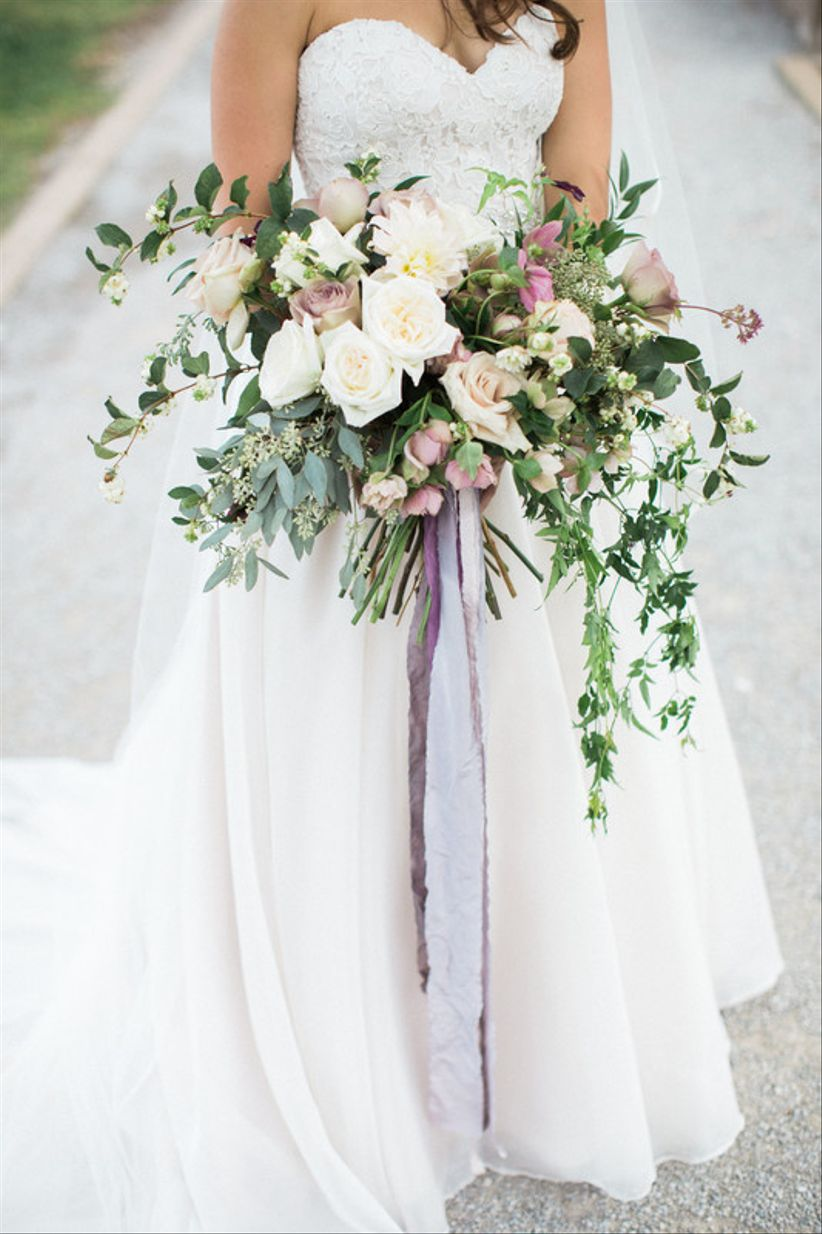oversized wedding bouquet with white flowers, greenery and long purple ribbons