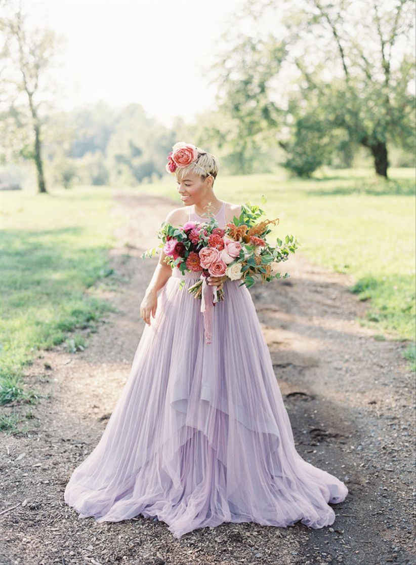 bride wearing lilac tulle wedding dress poses with oversized bouquet